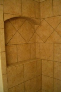 Ceramic corner niche with arched top and frame. On-point tile throughout