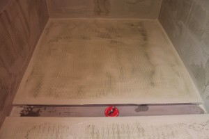 Installing the first layer of hydroban on shower floor